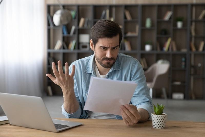 mężczyzna czyta pismo z odmową odszkodowania